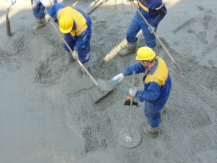 Construction workers spreading freshly poured concrete mix at the building site